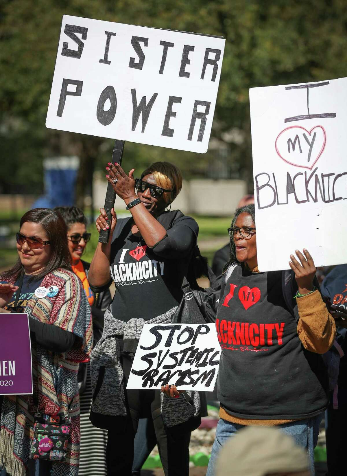 Gina Kay (center) and Quinnb Richardson (left) hold signs during the Third Annual March for Black Women at TSU Saturday, Feb. 22, 2020, in Houston.
