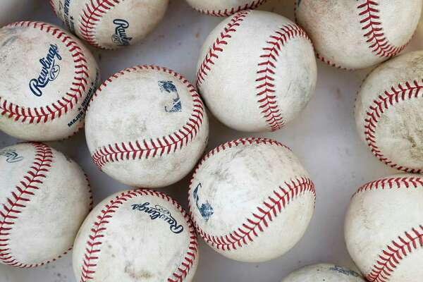 Scuffed up baseballs in a bucket during spring training at the Fitteam Ballpark of The Palm Beaches, in West Palm Beach, Saturday, Feb. 22, 2020.