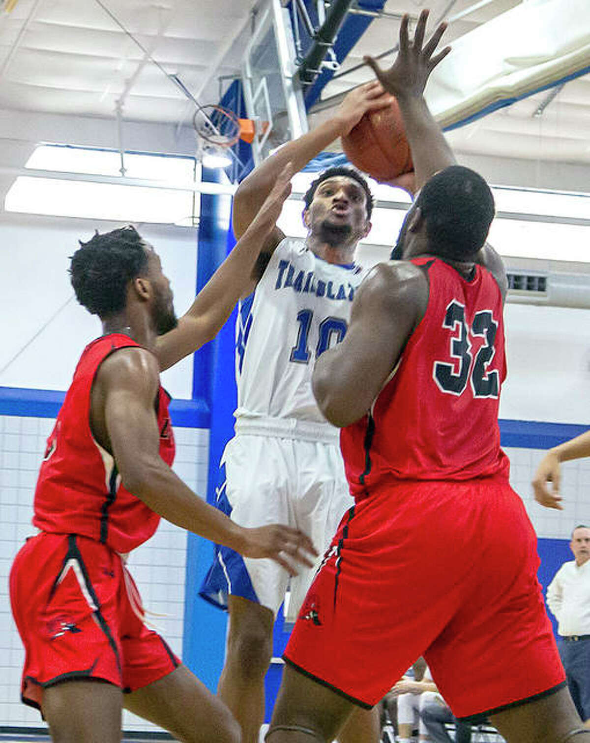 Ziven Clark, center, shots while being guarded by Lake Land's Christian Kapongo (32) Saturday.
