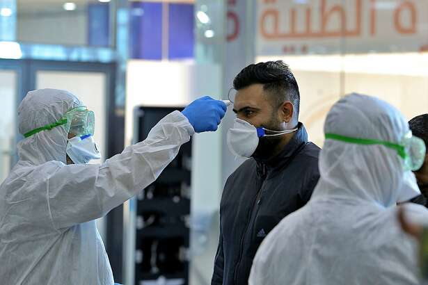 FILE - In this Friday, Feb. 21, 2020, file photo, medical staff check passengers arriving from Iran in the airport in Najaf, Iraq. Coronavirus-infected travelers from Iran already have been discovered in Lebanon and Canada. (AP Photo/Anmar Khalil, File)