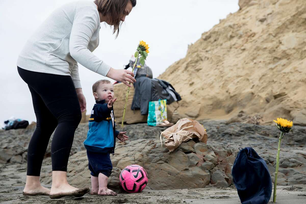 Kazmera Scarlet Lewis hands her son Benjamin, 5, a flower while standing near the spot where her sister Kyra Sunshine Scarlet's body was discovered one year prior at Fort Funston in San Francisco, Calif. Saturday, February 22, 2020. The family of Kyra Sunshine Scarlet, a 22-year-old who died in a landslide one year ago at Fort Funston, gathered on Saturday to honor the life of Kyra on the anniversary of her death