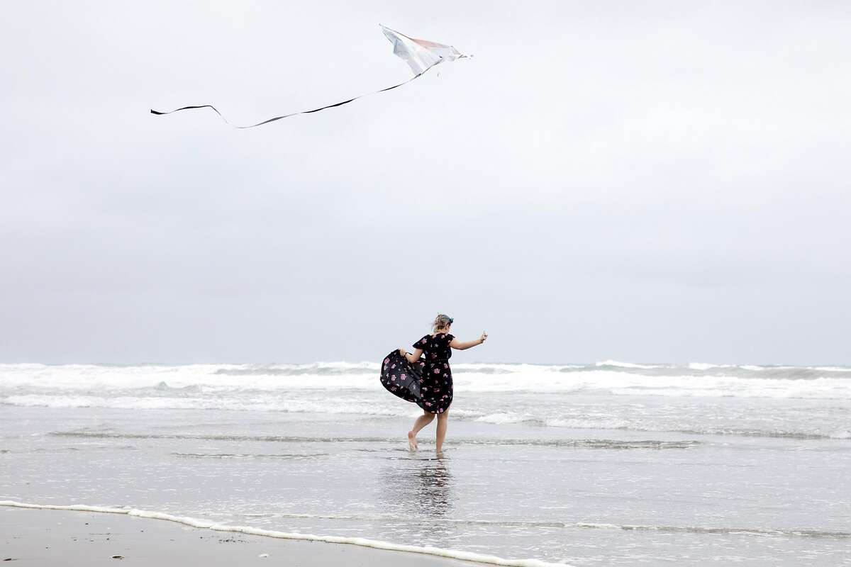 Zoee Scarlet, 16, frolics in the waves while flying a kite during a gathering to remember the life of her sister Kyra Sunshine Scarlet at Fort Funston in San Francisco, Calif. Saturday, February 22, 2020. The family of Kyra Sunshine Scarlet, a 22-year-old who died in a landslide one year ago at Fort Funston, gathered on Saturday to honor the life of Kyra on the anniversary of her death