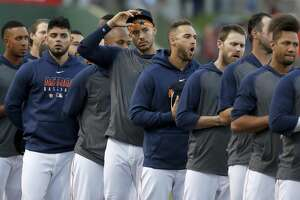 Houston Astros Carlos Correa and the rest of the team stand along the third base line during the National Anthem before the start of the Astros-Nationals spring training game at the Fitteam Ballpark of The Palm Beaches, in West Palm Beach, Saturday, Feb. 22, 2020.