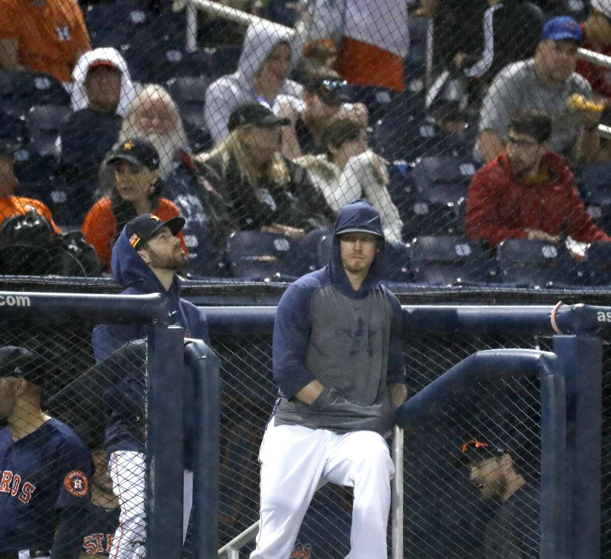 Houston Astros pitchers Chris Devenski and Austin Pruitt stand in the dugout as the rains started in the second inning during the Astros-Nationals spring training game at the Fitteam Ballpark of The Palm Beaches, in West Palm Beach, Saturday, Feb. 22, 2020.