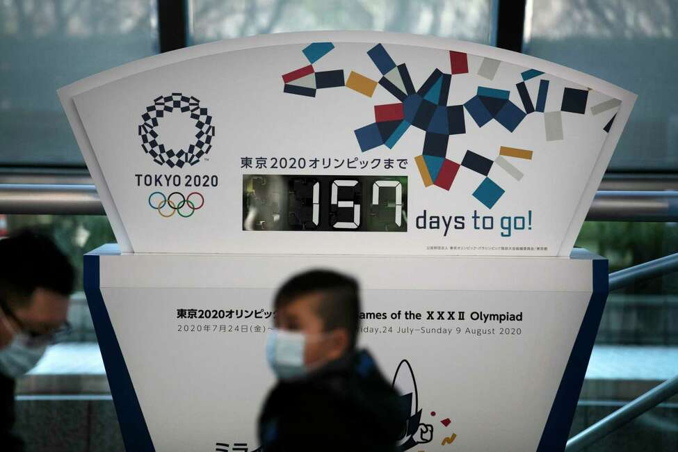 FILE - In this Tuesday, Feb. 18, 2020, file photo, people wearing masks sit in front of a countdown clock for the Tokyo 2020 Olympics in Tokyo. The Tokyo Olympics open in exactly five months on July 24. But the fast-spreading coronavirus from China is making Tokyo organizers very anxious. Three deaths have been reported in Japan with more than 700 cases, more than 600 from a cruise ship that docked in Japan. (AP Photo/Jae C. Hong, File)