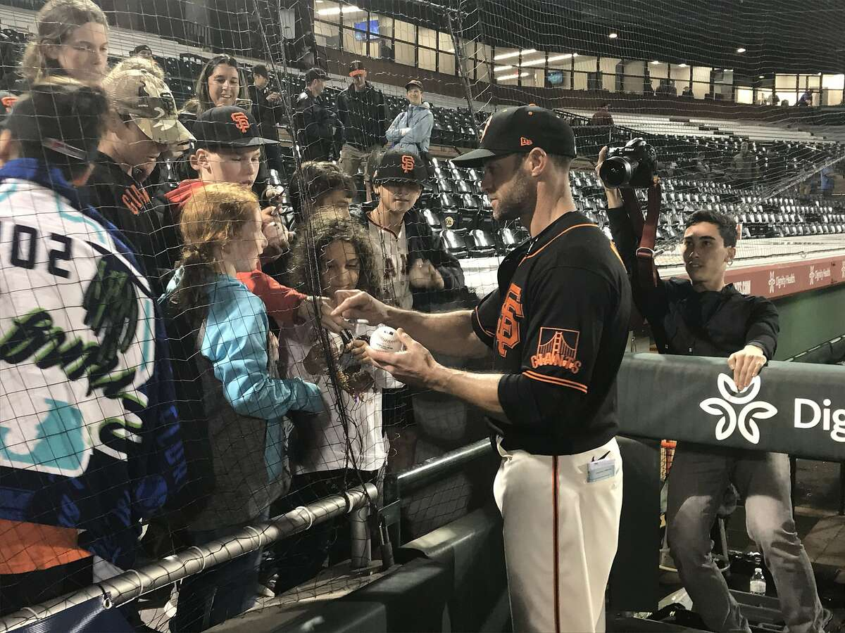Giants manager Gabe Kapler signs autographs at Scottsdale Stadium after Saturday's loss to the Dodgers in the Cactus League opener.