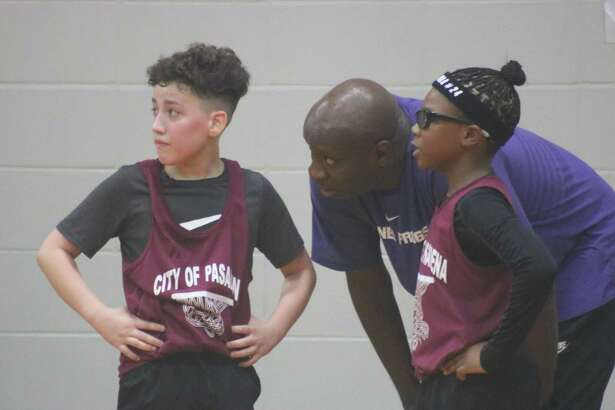 The Impact's Jonas Cruz (left) and D.J. Kirks talk it over with coach Fred Burke during their quarterfinal game at Bondy Intermediate Saturday afternoon. The two players combined for 24 points.