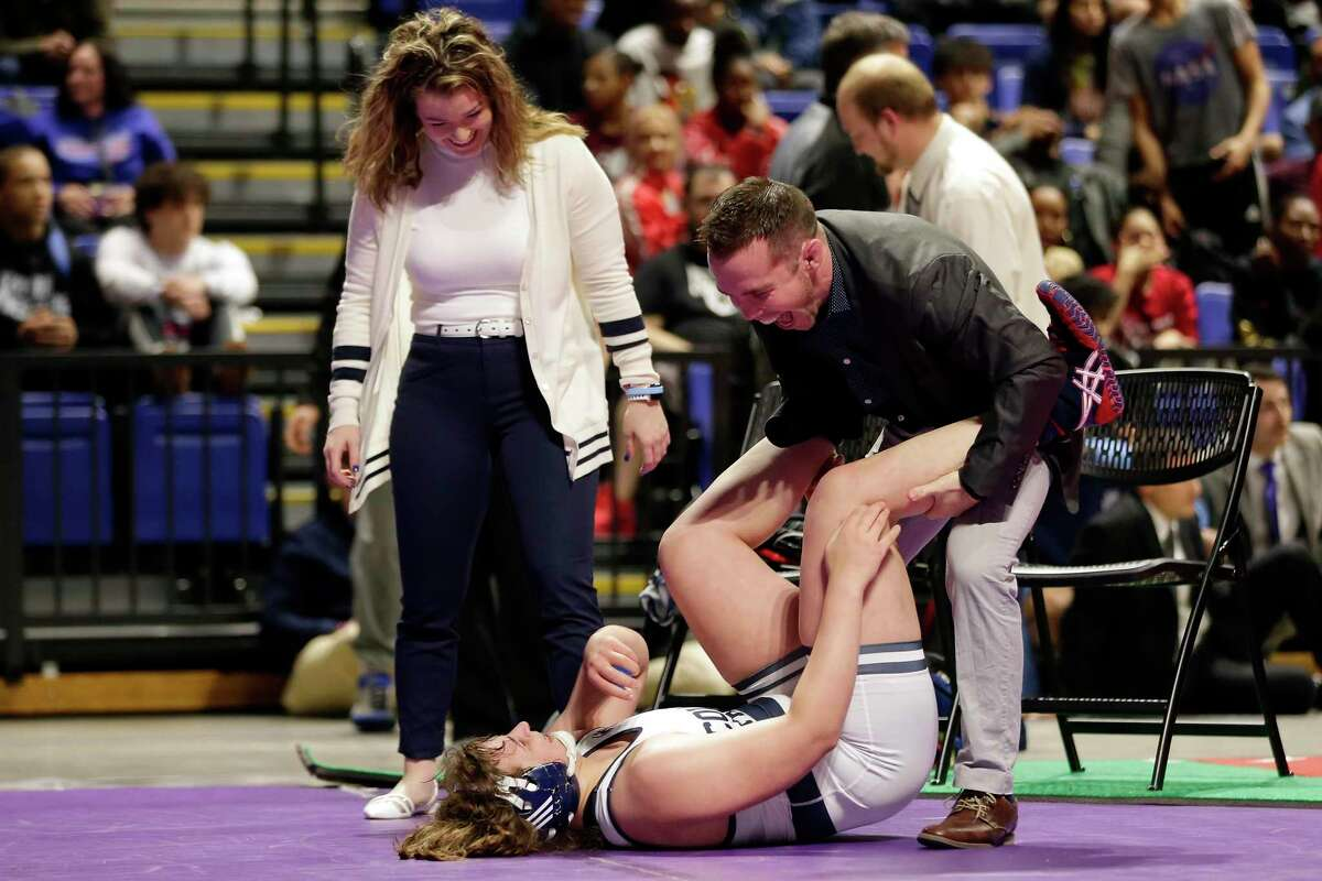 College Park's Brittyn Corbishley, on mat, celebrates with her coaches Erik Spjut, right, and Lindsey Spjut, left, after winning the Girls 6A-185lbs championship match of the state high school wrestling championships Saturday, Feb. 22, 2020 at the Berry Center in Cypress, TX.