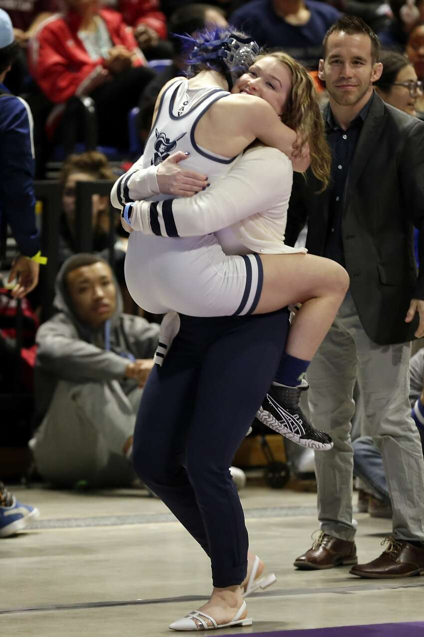 College Parks Olivia Degeorgio jumps into her coaches arms after defeating Tascosa's Mia Diaz in their Class 6A-95lbs championship match of the state high school wrestling championships Saturday, Feb. 22, 2020 at the Berry Center in Cypress, TX.