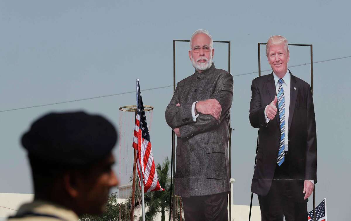A policeman stands near huge cut out images of U.S. President Donald Trump and Indian Prime Minister Narendra Modi displayed ahead of Trump's visit in Ahmedabad, India, Sunday, Feb. 23, 2020. The sun-baked northwestern Indian city was jostling with activity Sunday as workers cleaned roads, planted flowers and hoisted hundreds of billboards featuring President Donald Trump, a day ahead of his maiden two-day visit to India after Prime Minister Narendra Modi promised him a boisterous public reception.