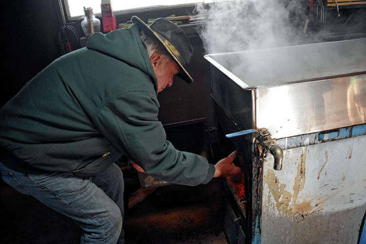 Pat Ward adds wood to the fire to boil sap.