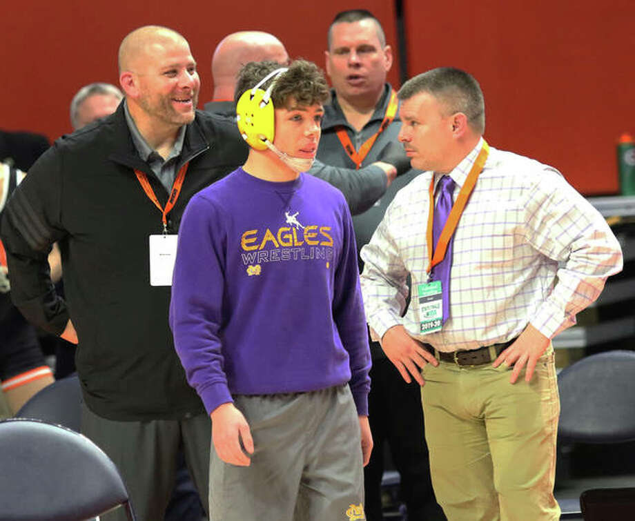 CM's Caleb Tyus waits for his Class 2A wrestling state championship match with Eagles coach Jeremy Christeson (left) and assistant Chad Young (right) on Saturday night at State Farm Center in Champaign. Photo: Greg Shashack / The Telegraph