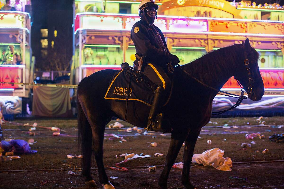 A police officer works the scene where a man was reportedly hit and killed by a float of the Krewe of Endymion parade in the runup to Mardi Gras in New Orleans, Saturday, Feb. 22, 2020. A person was struck by a float and fatally injured Saturday evening during one of the iconic parades of the Mardi Gras season in New Orleans, authorities said. It was the second death in days to mar this year's Carnival festivities. (Max Becherer/The Advocate via AP)