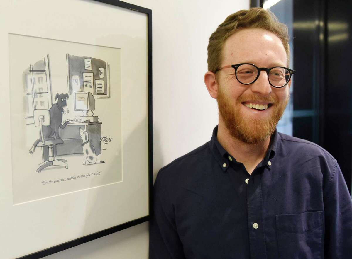 New Yorker staff writer Andrew Marantz poses beside a cartoon at the New Yorker office inside One World Trade Center in New York, N.Y. last week.