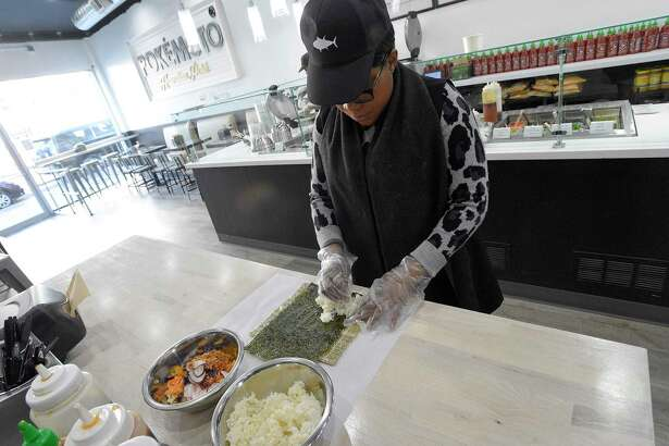 Gladys Longwa, co-owner of Pokemoto, prepares a poke burrito at the restaurant at 229 Main St., on Feb. 19, 2020 in downtown Stamford, Conn.