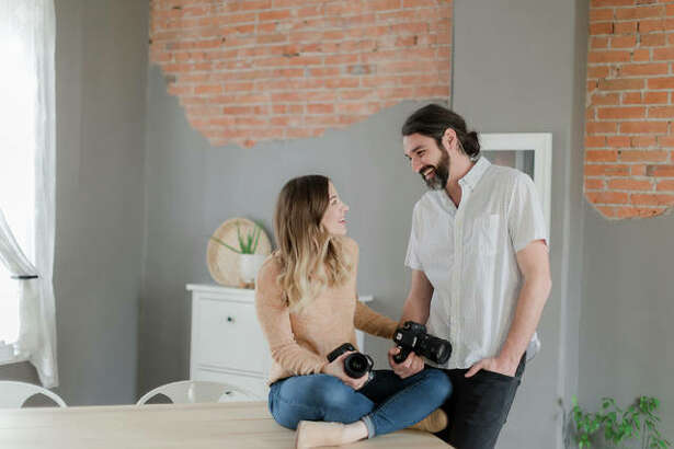 Melissa Lovell, left, and her husband, Shea Lovell, who founded their family owned business, Capture Photography, in 2006, hold the tools of their trade at their Edwardsville home.