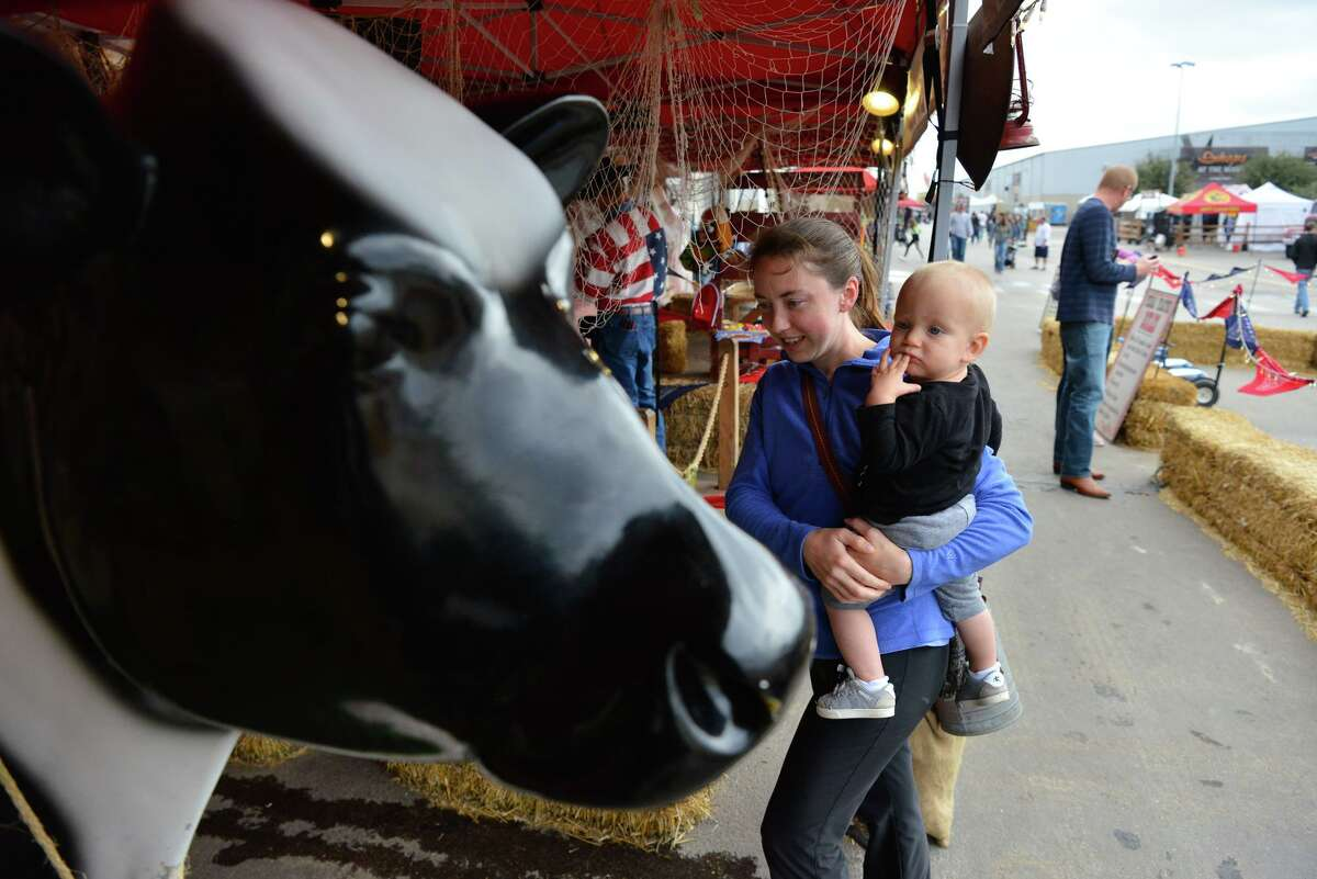 Jackson Mack, 14 months, and his mother Rachel Mack, check out a milking exhibit in the Cowboy Boot Camp section of the San Antonio Stock Show and Rodeo, which ended its' 2020 run Sunday with Family Day.