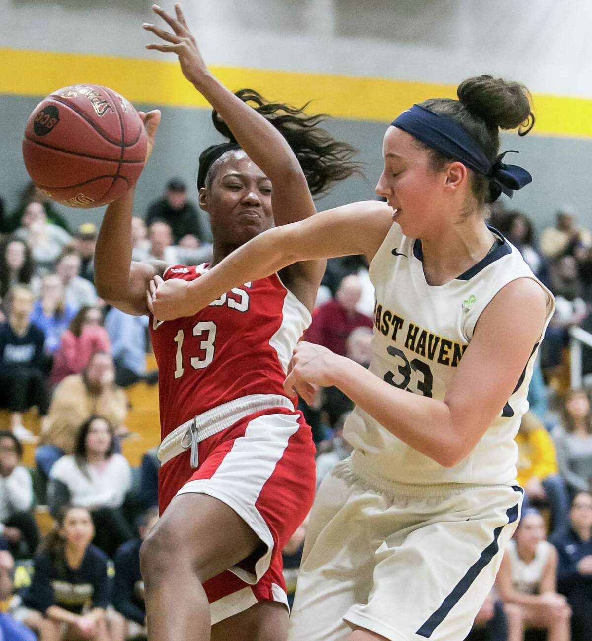(John Vanacore/For Hearst Connecicut Media) East Haven's Taylor Salato and Cross's Anajija Ricks battle for a rebound during the SCC Semi Final game Monday night in Milford.