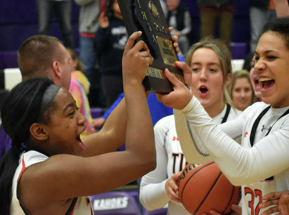 Edwardsville's Quierra Love, left, and Maria Smith celebrate with the Class 4A Collinsville Regional championship plaque on Friday. Photo: Matt Kamp|The Intelligencer