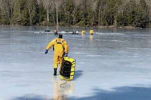 Torrington firefighters rescuing fishermen who had fallen through the ice on Burr Mountain Pond this morning.