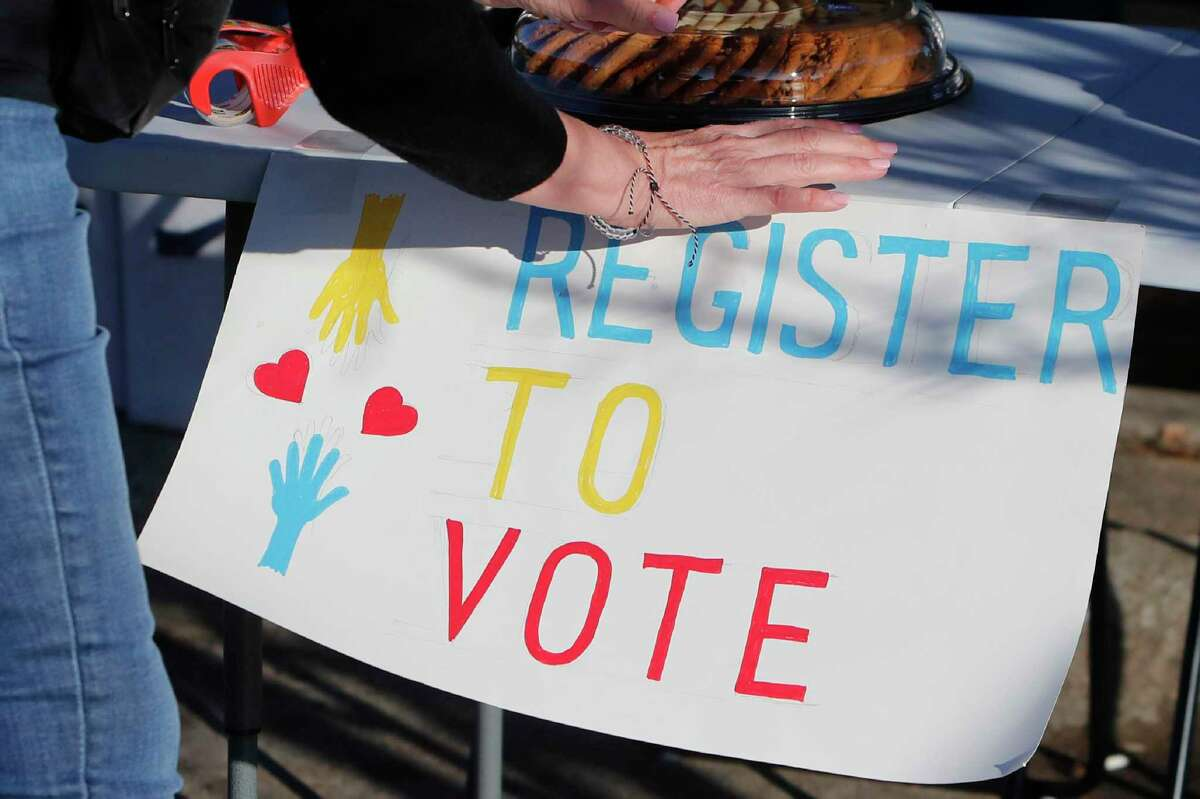 A voting drive volunteer sets up a table in Texas. Democrats are anxious about the coming presidential election and Republicans are more likely to be excited about it. That's the finding of a new poll from The Associated Press-NORC Center for Public Affairs Research.