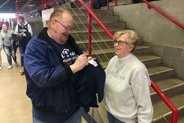 "Tom ""Big Red"" Emery signs an autograph for Manchester's Ellen Daley prior to UConn's game with USF on Sunday at Gampel Pavilion."