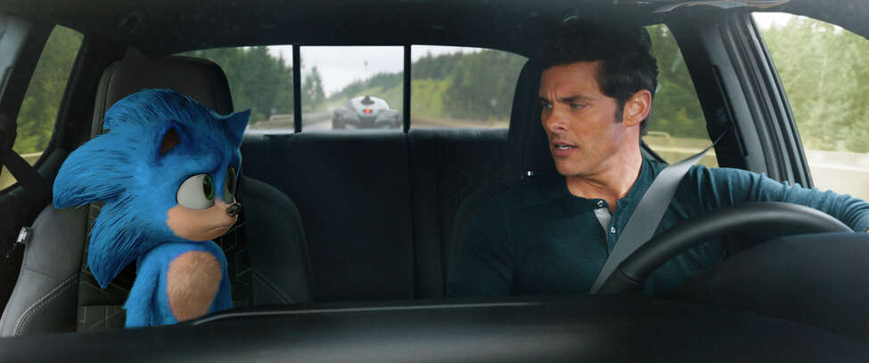 This image released by Paramount Pictures shows Sonic, voiced by Ben Schwartz, left, and James Marsden in a scene from