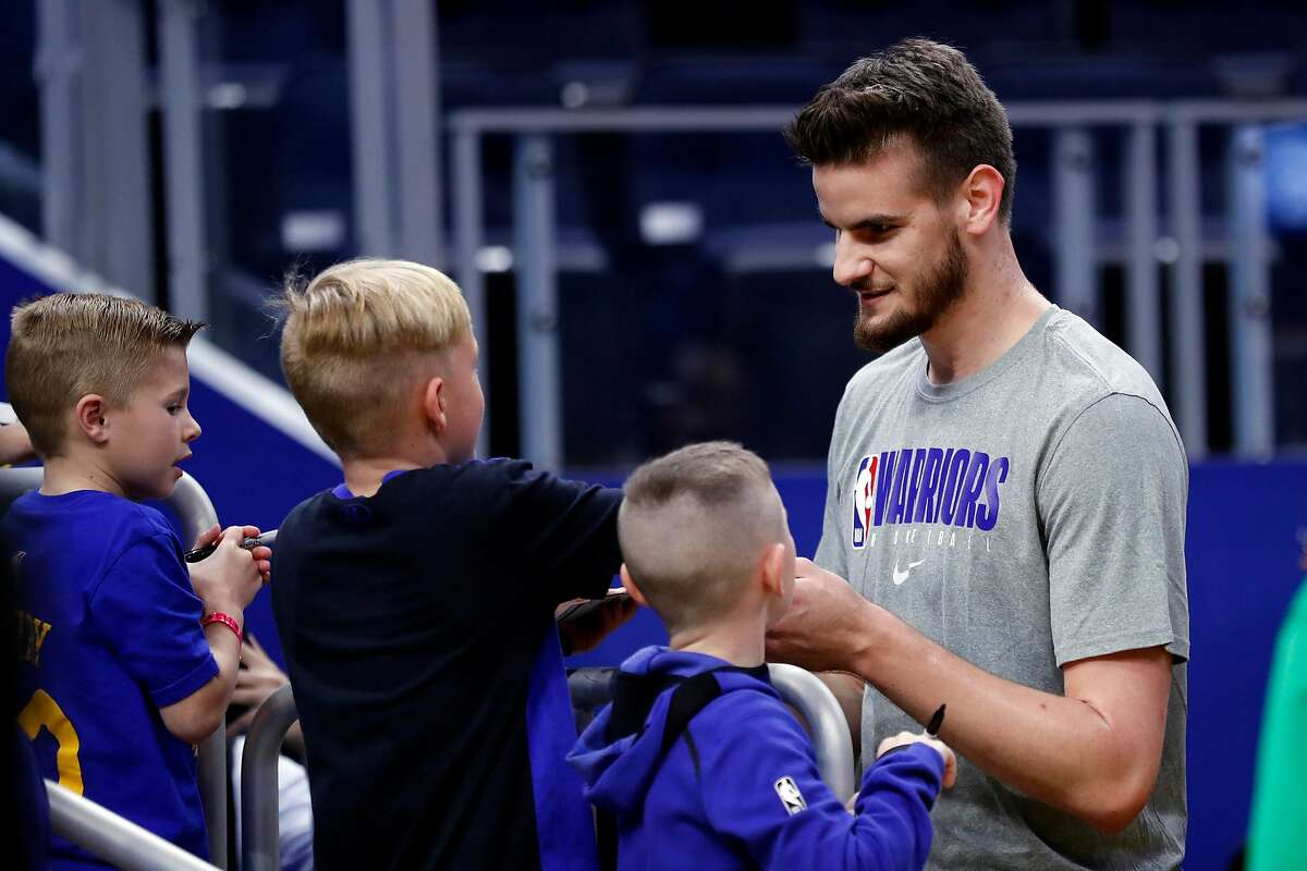 Golden State Warriors' Dragan Bender signs an autograph after warming up before Warriors play New Orleans Pelicans during NBA game at Chase Center in San Francisco, Calif., on Sunday, February 23, 2020.