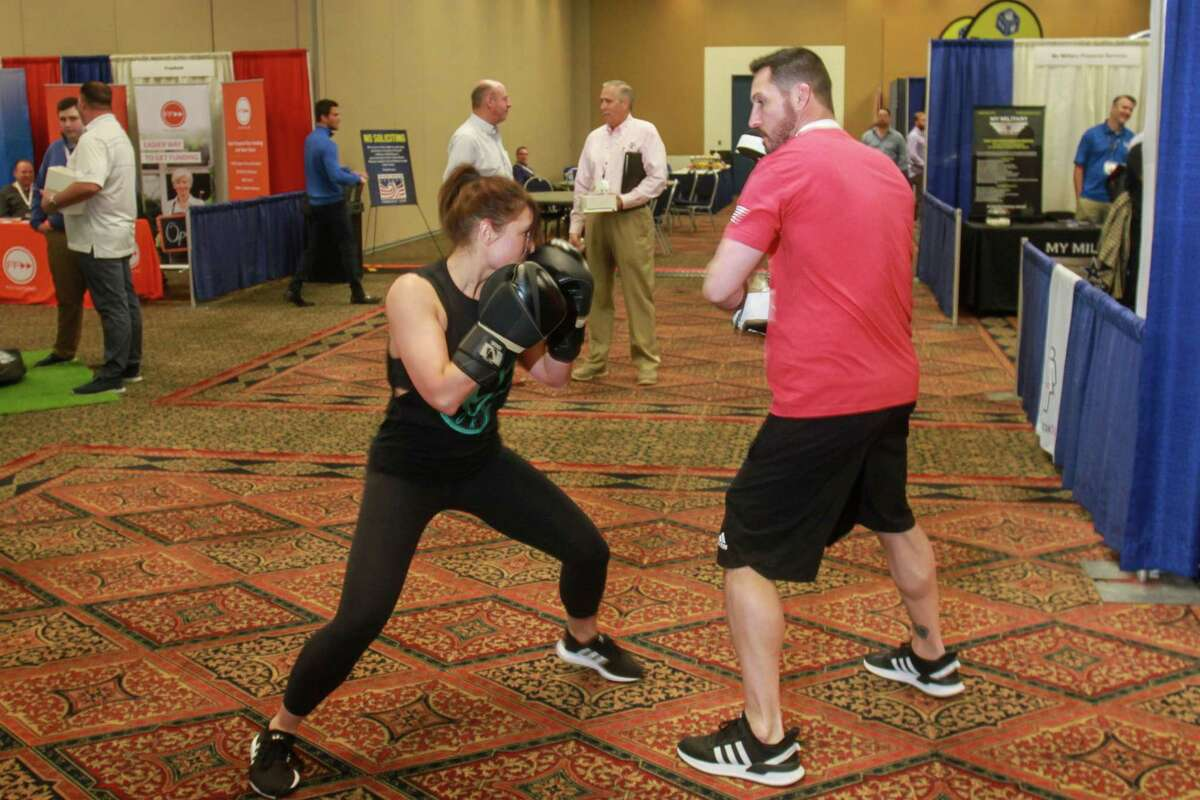 Andrew Scott, co-founder and national head coach for Legends Boxing, during a demonstration with his wife, Kelly, at the Great American Franchise Expo in Stafford on February 23, 2020. Kelly is hitting Andrew's focus gloves.