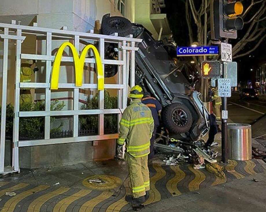 A man was hospitalized and his Jeep came to rest against a McDonald's after its fall from a garage. Photo: Santa Monica Fire Department