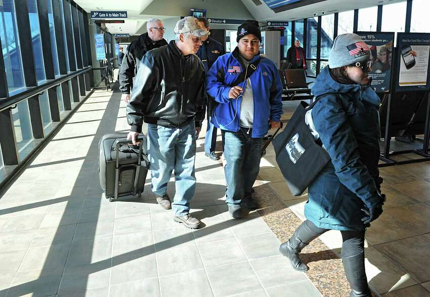 Tim Forbes, left, of the Wounded Warrior committee picks up Wounded Warrior Sgt. Gonzolo Duran, center, and his fiancee Rosa Perelta, right, of the Dominican Republic, at the Rensselaer Train Station on Thursday March 6, 2014 in Rensselaer, N.Y. Duran will be participating in STRIDE's Wounded Warrior Snowfest this weekend, and will be honored tomorrow night at the Troy Hilton Garden Inn along with 10 other Wounded Warriors before being transported to Jiminy Peak Mountain Resort for a weekend of rehabilitative skiing or snowboarding. (Lori Van Buren / Times Union)