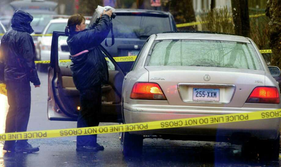 Det Hollie Tutrani from the Bureau of Identification unit of the New Haven Police Dept. takes photos of a car involved in a shooting, on Lilac St. Mara Lavitt/New Haven Register 3/12/13