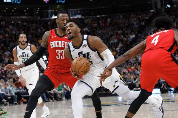 The Rockets' Robert Covington (33) and Danuel House Jr. (4) try to impede Donovan Mitchell's path to the basket in Saturday's win at Utah.
