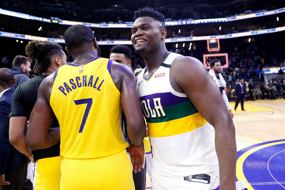 New Orleans Pelicans' Zion Williamson greets Golden State Warriors' Eric Paschall after Pelicans' 115-101 win in NBA game at Chase Center in San Francisco, Calif., on Sunday, February 23, 2020.