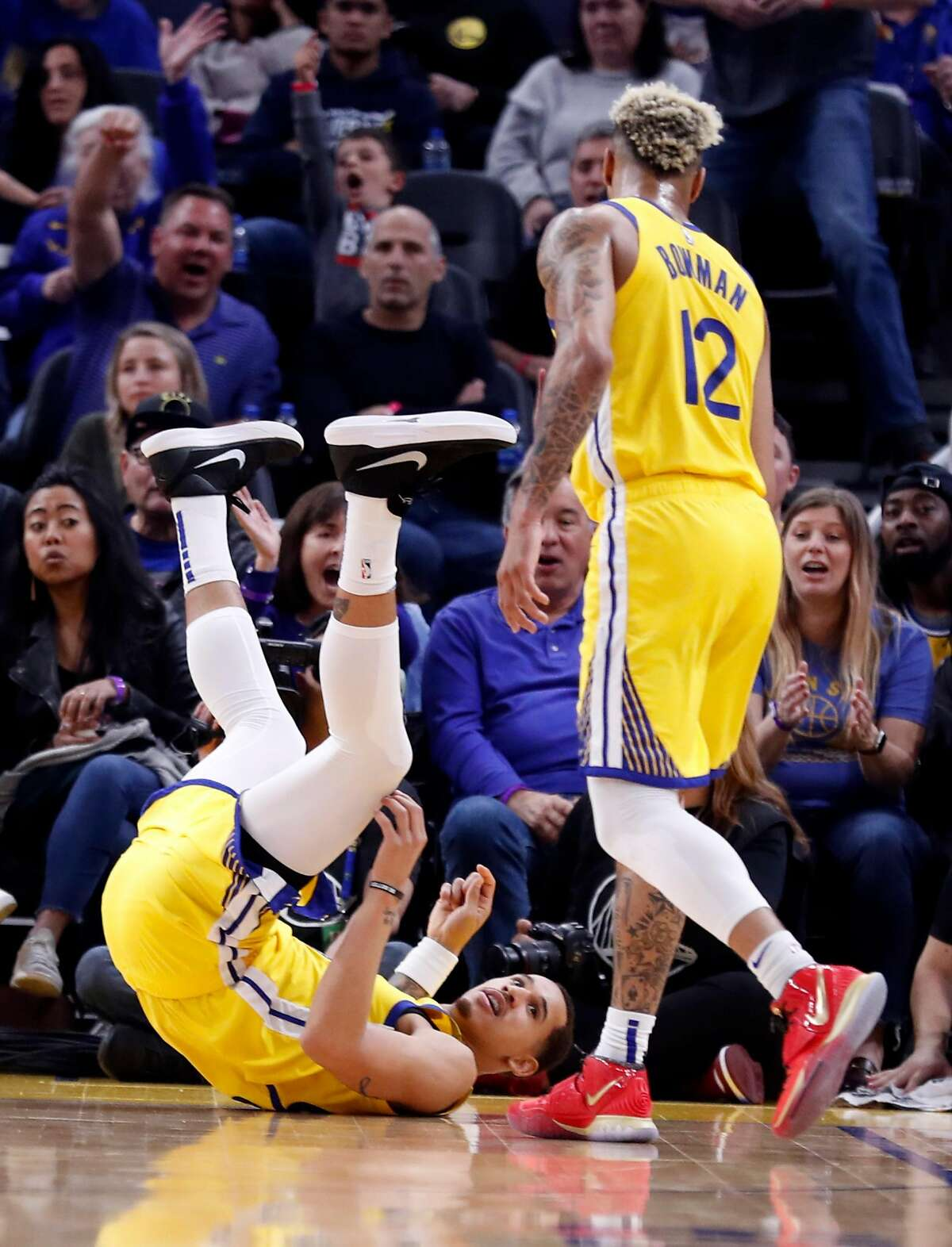 Golden State Warriors' Juan Toscano-Anderson looks up at Ky Bowman after being fouled while scoring during 4th quarter of New Orleans Pelicans' 115-101 win in NBA game at Chase Center in San Francisco, Calif., on Sunday, February 23, 2020.