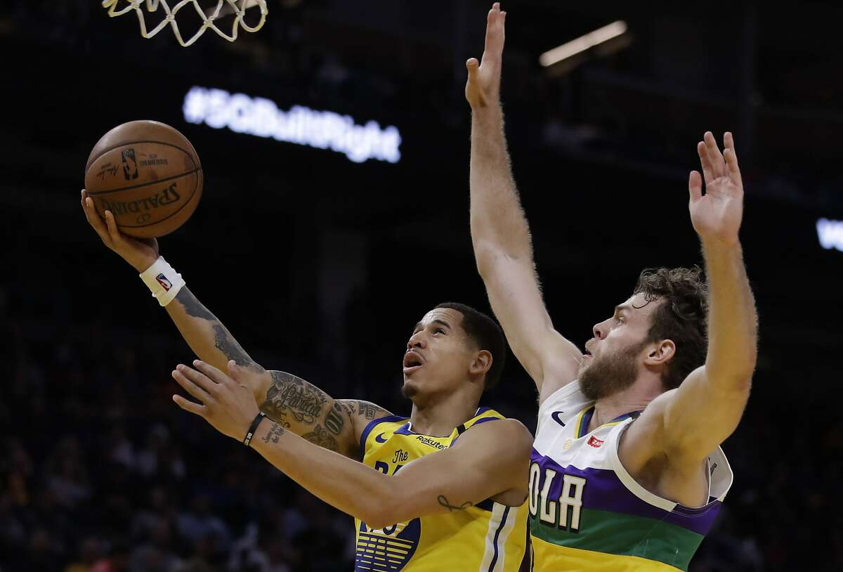 Golden State Warriors' Juan Toscano-Anderson, left, lays up a shot past New Orleans Pelicans' Nicolo Melli in the second half of an NBA basketball game Sunday, Feb. 23, 2020, in San Francisco. (AP Photo/Ben Margot)