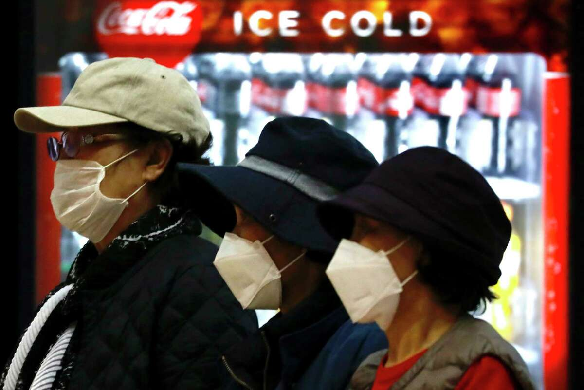 Tourists from Korea wearing protective masks walk with their belongings while waiting for a flight back to South Korea at the Ben Gurion airport near Tel Aviv, Israel, Monday, Feb. 24, 2020.  On Thursday, Israel Science and Technology Minister Ofir Akunis said researchers were developing a vaccine for COVID-19 that could be ready in 90 days.
