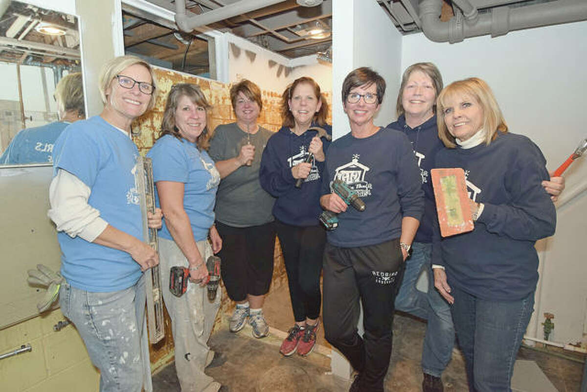 Girls in the Garage take a break while retiling a shower in a group member's house. They are Lori Hartz (from left), Judy Tighe, Tammy Middleton, Barb Whalen, Lisa Kluge, Anne Jackson and Daphne Spradlin.