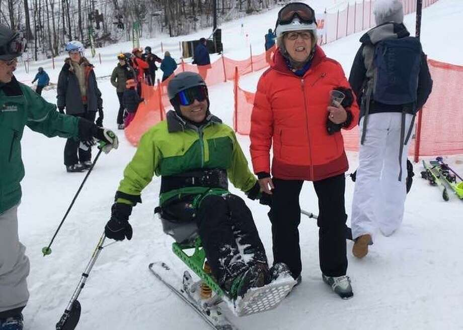 Jose Morales of Monroe, Conn., is greeted by Lissi Gray of Wilton after a run down Windham Mountain on a monoski in 2019. Morales, who was paralyzed in a ladder accident, will ski in the 20th Michael Gray Memorial Ski and Snowboard Race on March 7. Lissi Gray was Michael Gray's mother, for whom the race is named. Photo: Contributed Photo / Gray Family / Wilton Bulletin Contributed