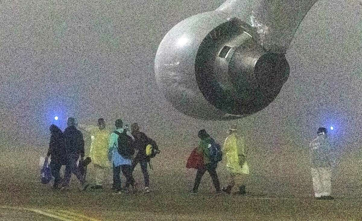 Amid heavy fog, American passengers evacuated from the Diamond Princess cruise ship in Japan disembark Feb. 17, 2020, from a plane at Kelly Field. The group of 144 passengers arrived in San Antonio to undergo quarantine at a hotel on Joint Base San Antonio-Lackland.