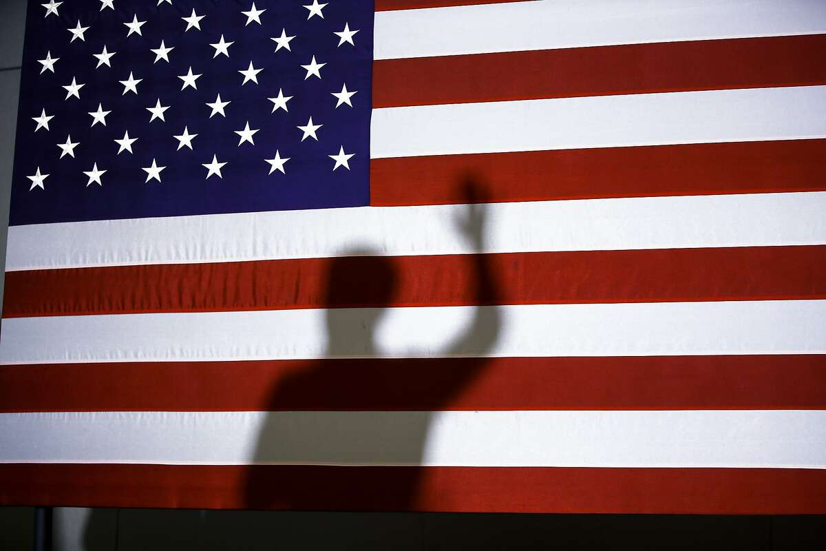 Democratic presidential candidate former South Bend, Ind., Mayor Pete Buttigieg's shadow is cast on an American Flag as he speaks during a campaign event, Monday, Feb. 10, 2020, in Plymouth, N.H. (AP Photo/Matt Rourke)