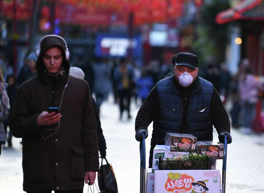 A worker wears a surgical face mask in London's Chinatown district on Feb. 13, 2020. The city is hosting IP Week, where the talk of the industry will be the effect of the coronavirus on oil demand. Photo: DANIEL LEAL-OLIVAS, AFP Via Getty Images / AFP or licensors