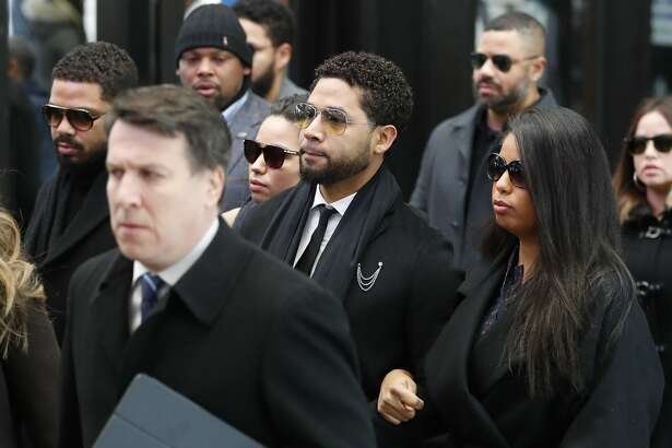 "Former ""Empire"" actor Jussie Smollett, center, arrives for an initial court appearance Monday, Feb. 24, 2020, at the Leighton Criminal Courthouse in Chicago, on a new set of charges alleging that he lied to police about being targeted in a racist and homophobic attack in downtown Chicago early last year. (AP Photo/Charles Rex Arbogast)"