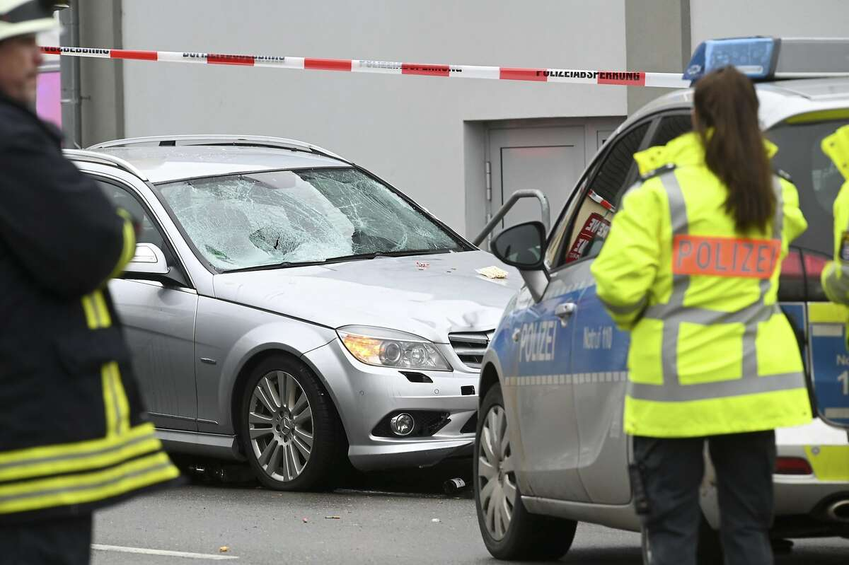 Police stand next to the scene of the accident with the car that is said to have crashed into a carnival parade in Volkmarsen, central Germany, Monday, Feb. 24, 2020. Several people have been injured, according to the police. The driver had been arrested by the police.