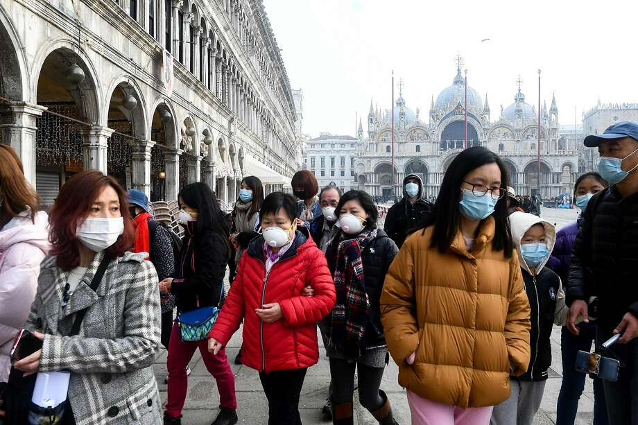 Tourists wearing protective masks visit St. Mark's Square in Venice. Police manned checkpoints around a dozen quarantined towns in Italy's north on Monday as authorities sought to contain the outbreak. Photo: Andrea Pattaro / AFP Via Getty Images