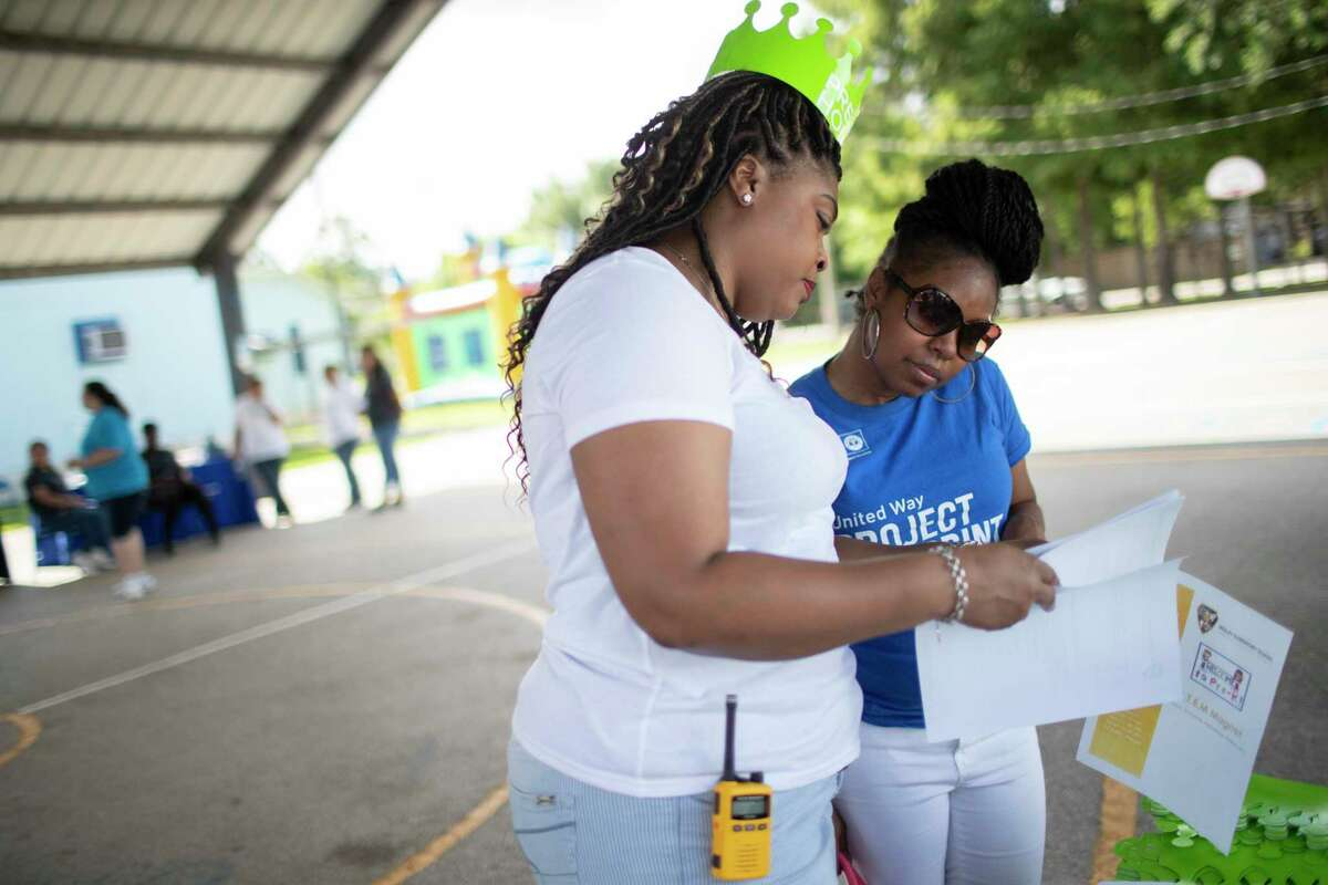 In this 2019 file photo, Wesley Elementary School assistant principal LaKia Jackson, left, shares information with Tamira Samuel, who planned to enroll her twin boys into pre-kindergarten at the northside campus. The Houston Education Research Consortium has studied pre-kindergarten enrollment trends in Houston ISD, part of its history with the district that will underpin a wide-ranging equity study over the next year.
