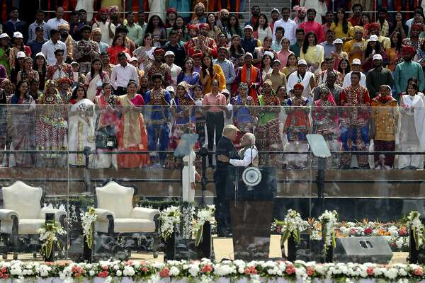 Indians watch U.S. President Donald Trump and Indian Prime Minister Narendra Modi hug each other after they arrive to attend the 'Namaste Trump' event at Sardar Patel Stadium in Ahmedabad, India, Monday, Feb. 24, 2020. Basking in adulation from a massive, colorful crowd, President Donald Trump and India's Prime Minister Narendra Modi lavished each other with praise Monday in a reaffirmation of U.S.-India ties as the subcontinent poured on the pageantry in a joyful welcome for the U.S. president.