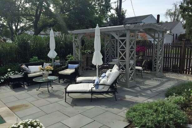 The fenced backyard has a pergola and patio.
