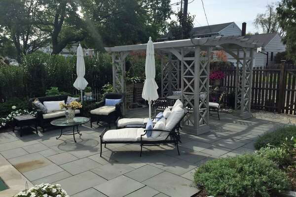 The fenced backyard has a pergola and patio.