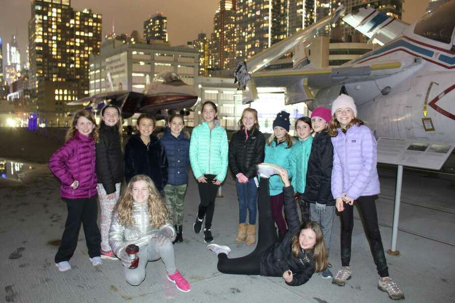 New Canaan Girl Scouts get a close look at aircraft on the Intrepid Sea, Air and Space Museum in New York City recently. In front are Olivia Barbera and Maya Lundberg. In back are Brenna Miller, Elle Culliss, Mis Ross, Lucy Casey, Sophie Dunlap, Katie Scholtz, Ellie Ikard, Ellie Whinery, Devin Boulanger and Abby Dunlap, Photo: Girl Scouts / Contributed Photo / New Canaan Advertiser Contributed